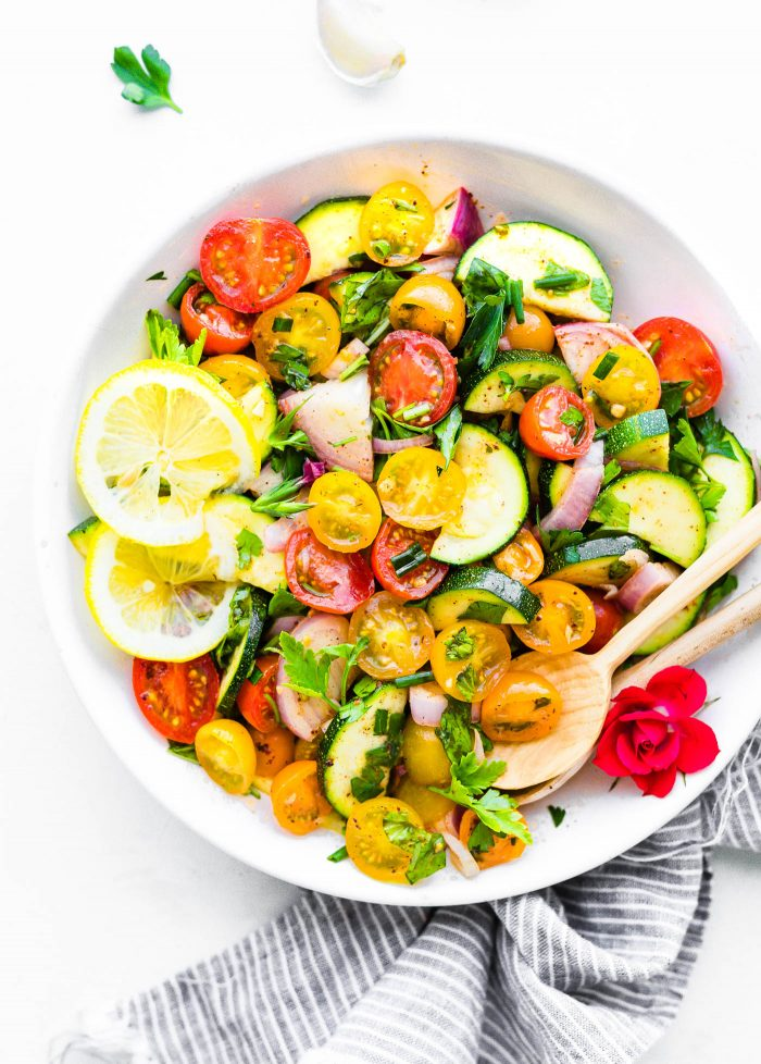 tomato zucchini salad in white bowl with serving spoon