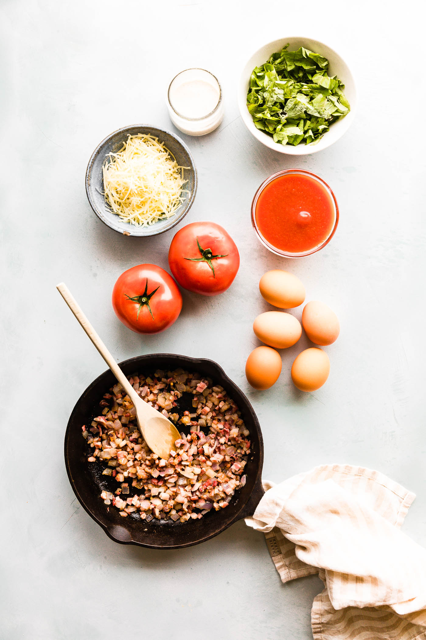 ingredients needed to make an Italian egg bake recipe. Shown: farm fresh eggs, fresh tomatoes, unsweetened almond milk, Parmesan cheese, tomato sauce, fresh herbs all surrounding nitrate free pancetta cooking in a cast iron skillet