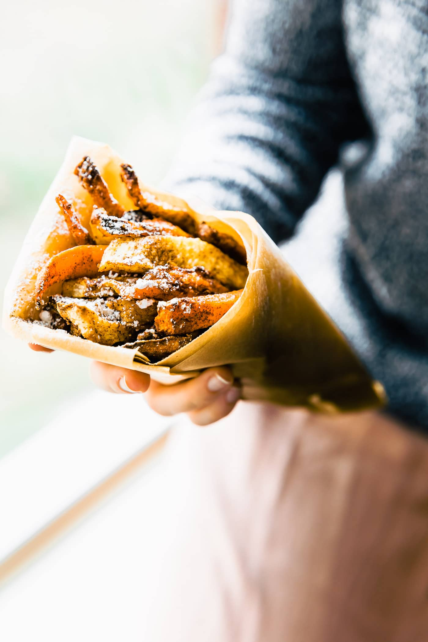 woman holding air fried sweet potato fries served in parchment paper cone