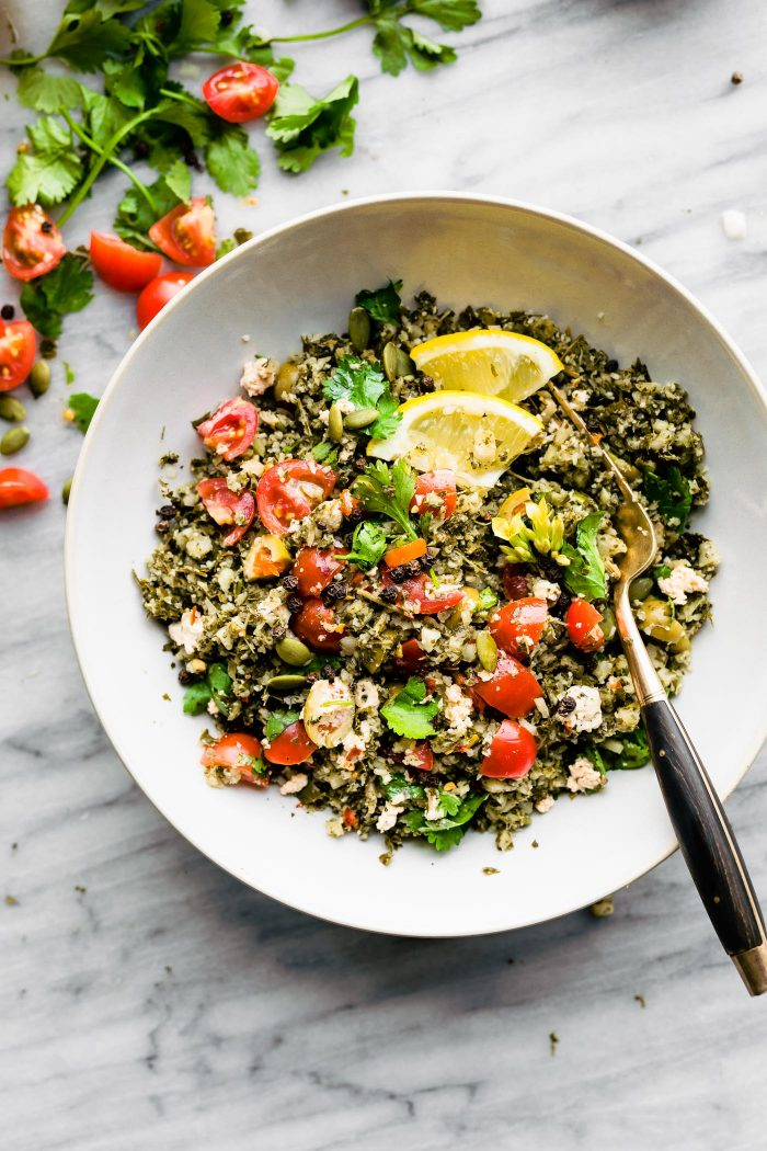 overhead image: Greek cauliflower salad in white bowl with serving spoon