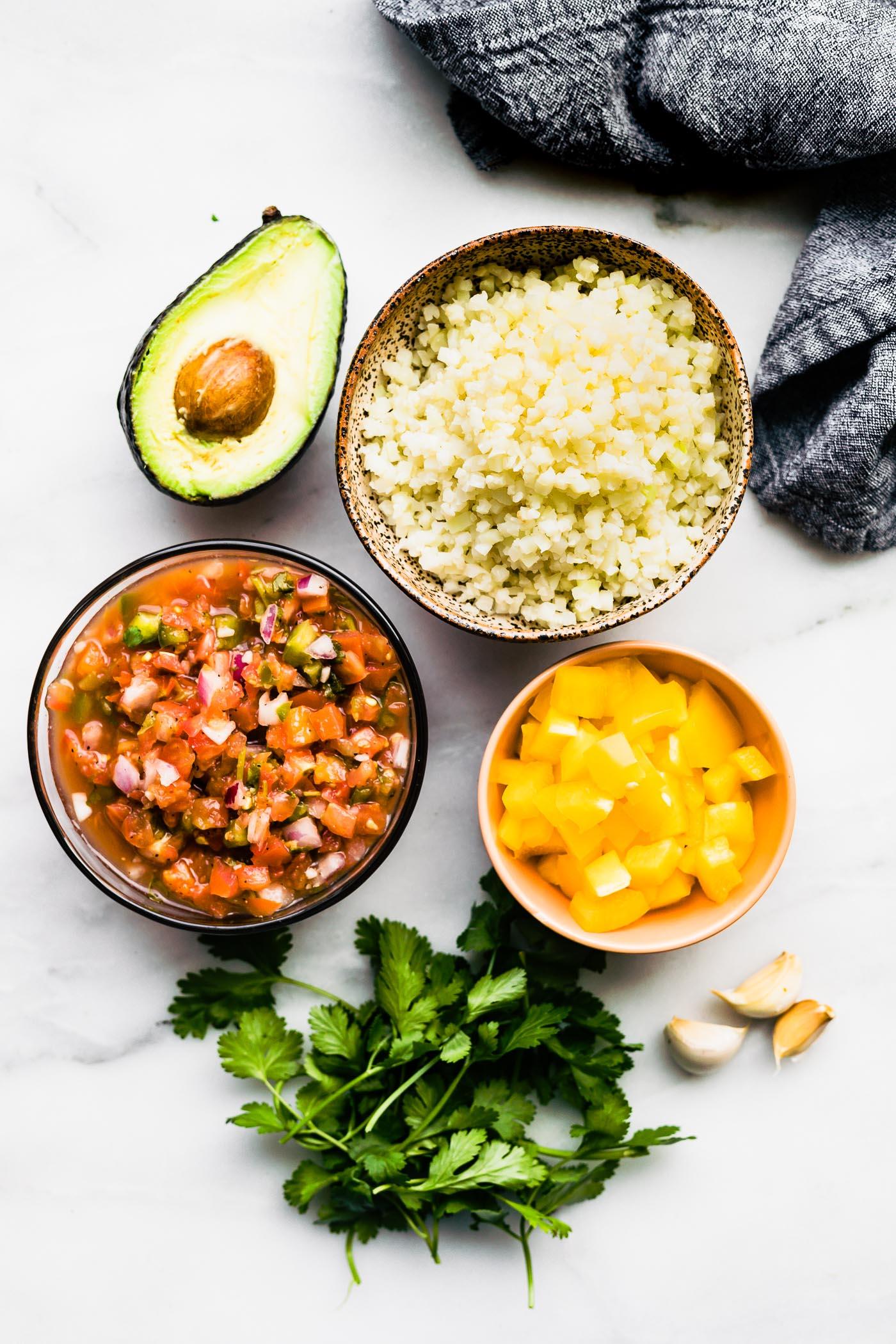 peppers, rice, avocado, pcio de gallo, and herbs on a table