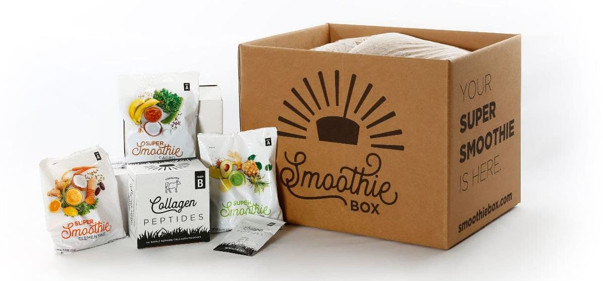 "cardboard box with ""SmoothieBox"" written on the side, with packets of smoothie ingredients"
