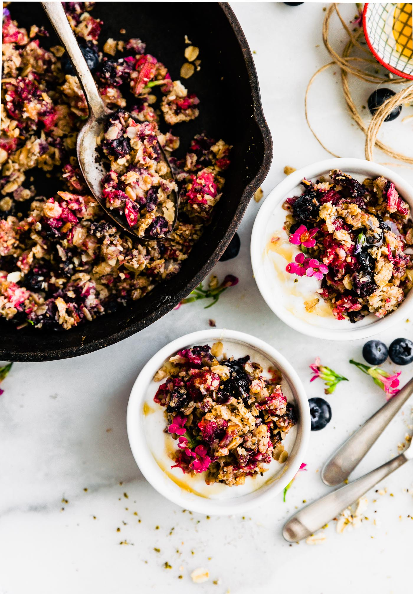 vegan fruit crumble with fresh berries in cast iron skillet