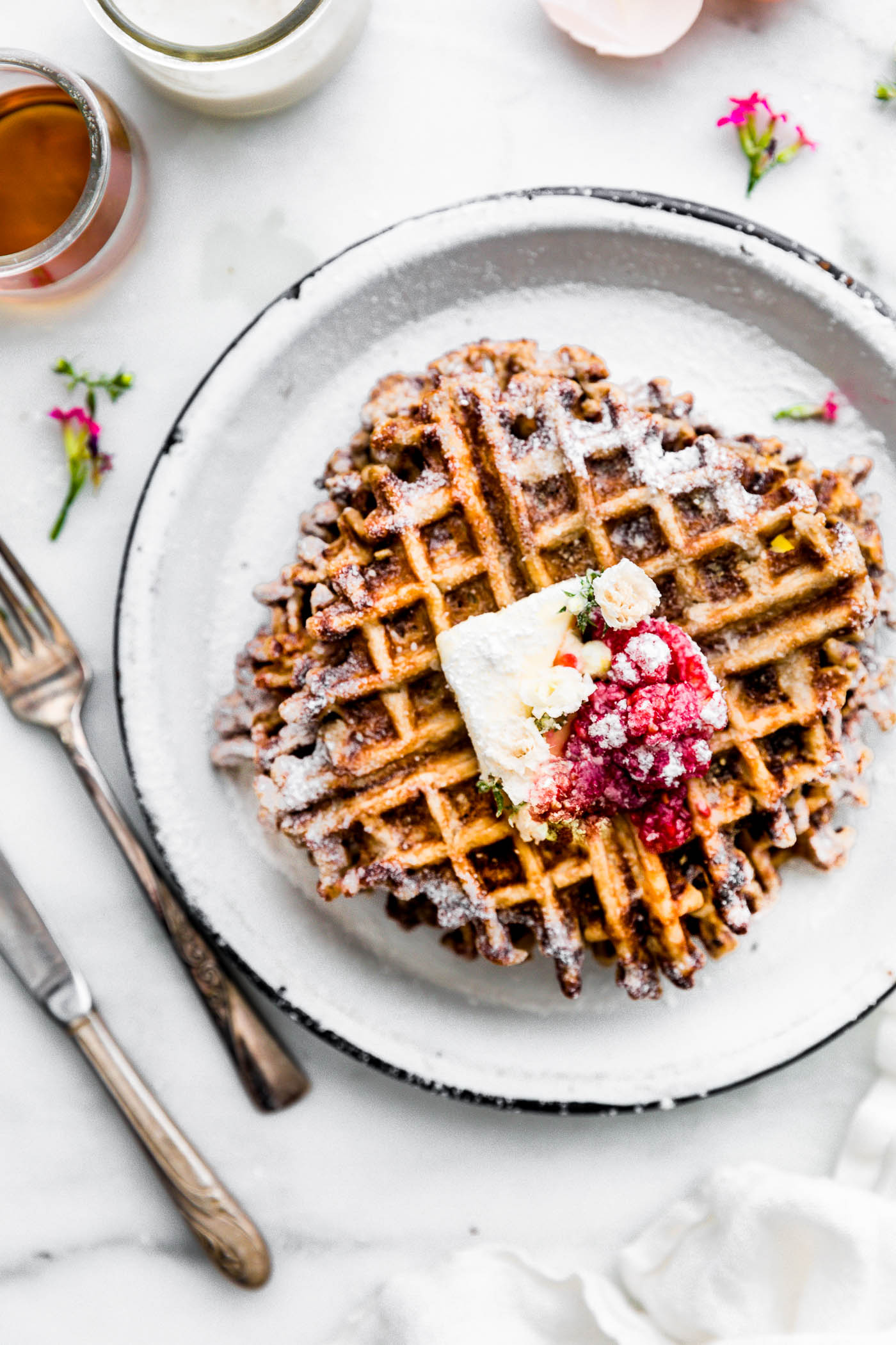 paleo waffles topped with fresh berries on a white plate