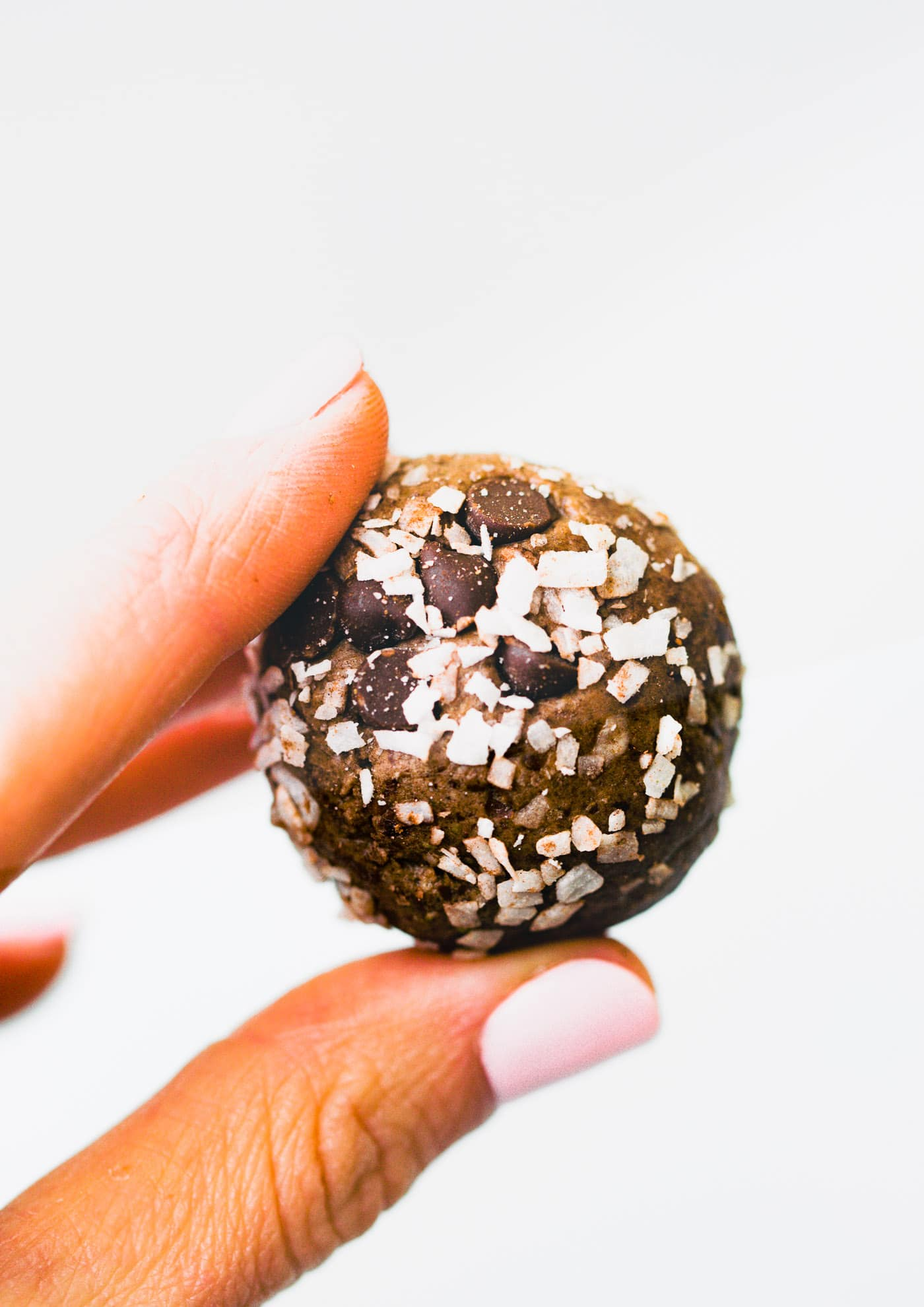 woman's fingers holding a chocolate coconut no bake protein snack