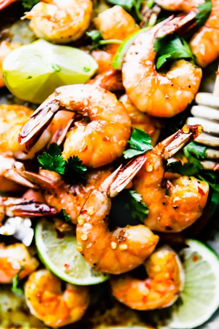 plate of tail-on baked shrimp suurounded by lime slices