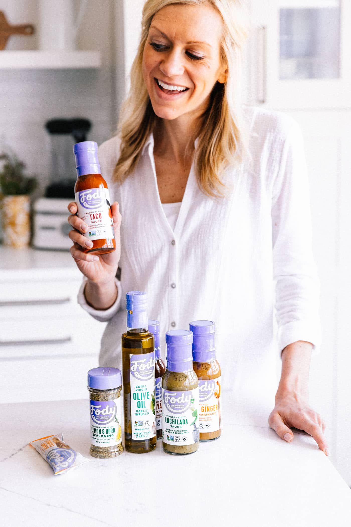 blonde-haired woman in kitchen with gut healthy foods from Fody Foods