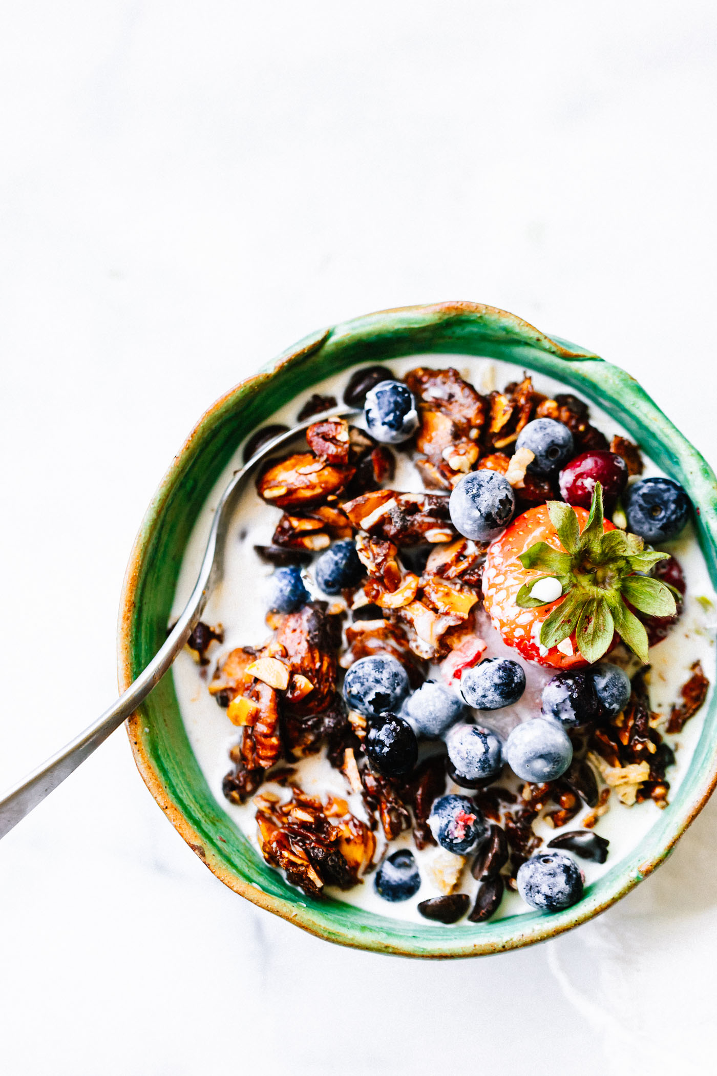 low sugar granola clusters in cereal bowl with blueberries and milk