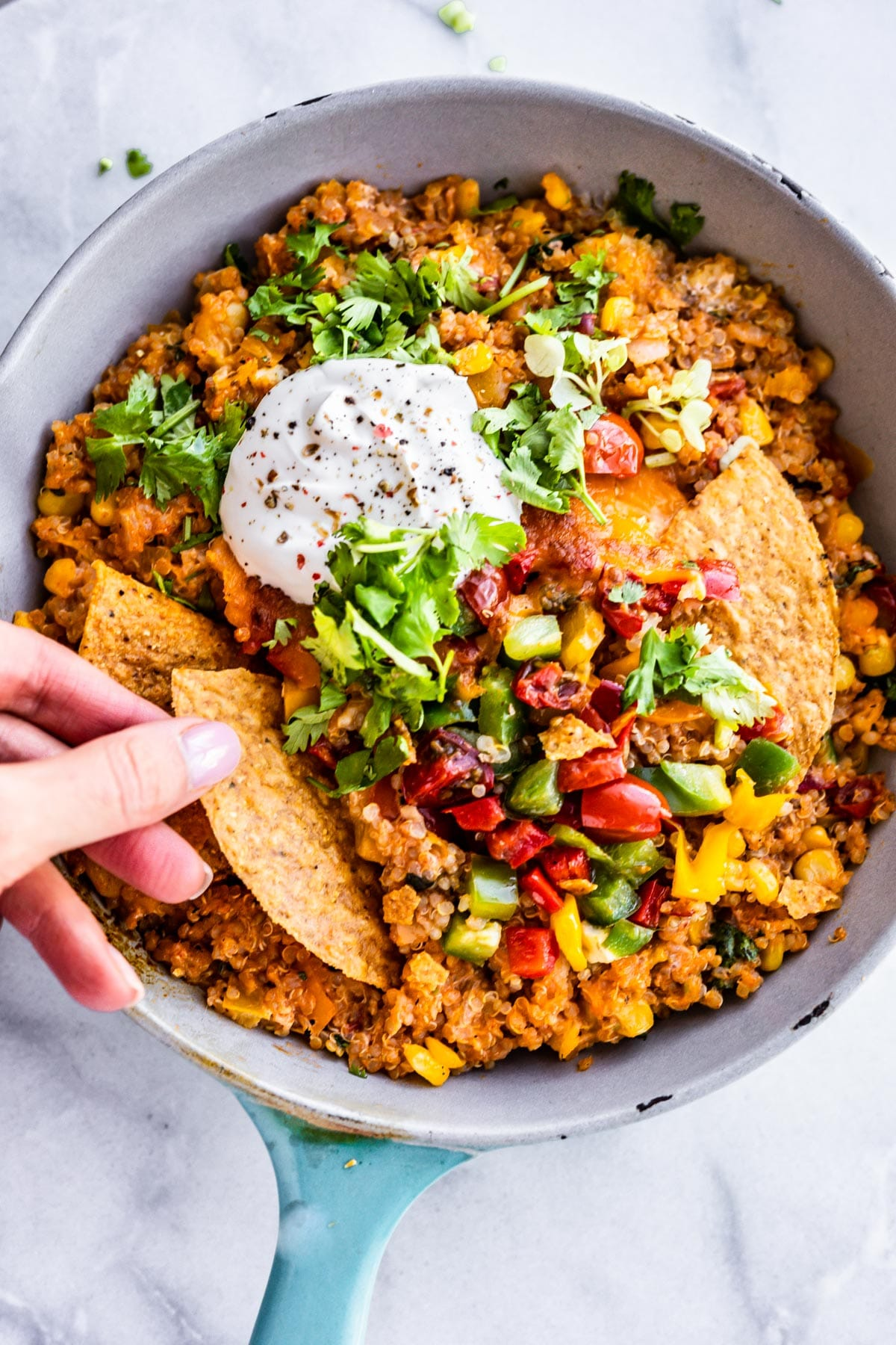 mexican dinner skillet with hands and chips