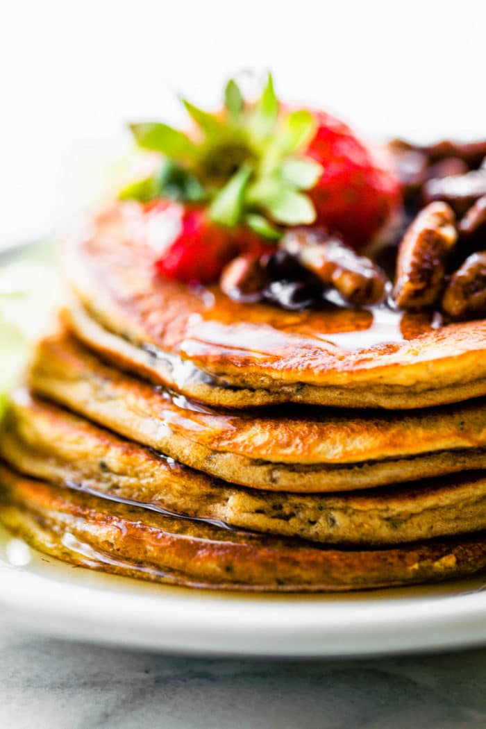 paleo pancakes up close on plate with berries and nuts on top