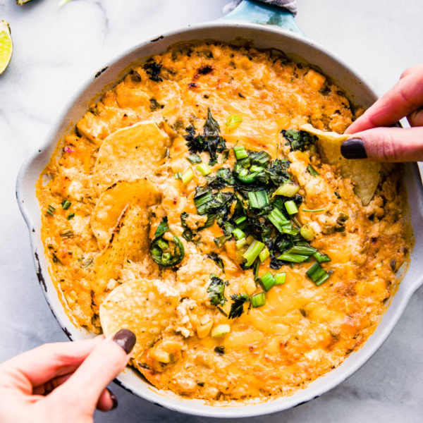hands dipping chips into roasted jalapeno hot crab dip