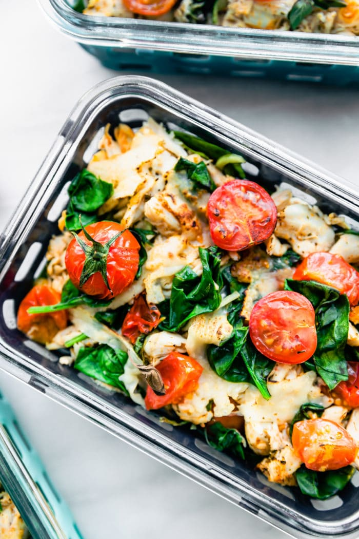 keto chicken dinner with spinach and tomatoes in meal prep container