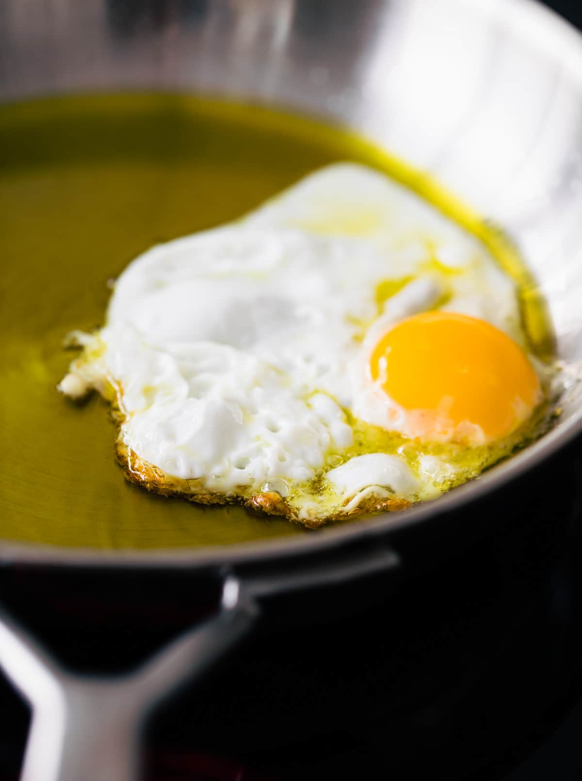 close up of fried egg in extra virgin olive oil