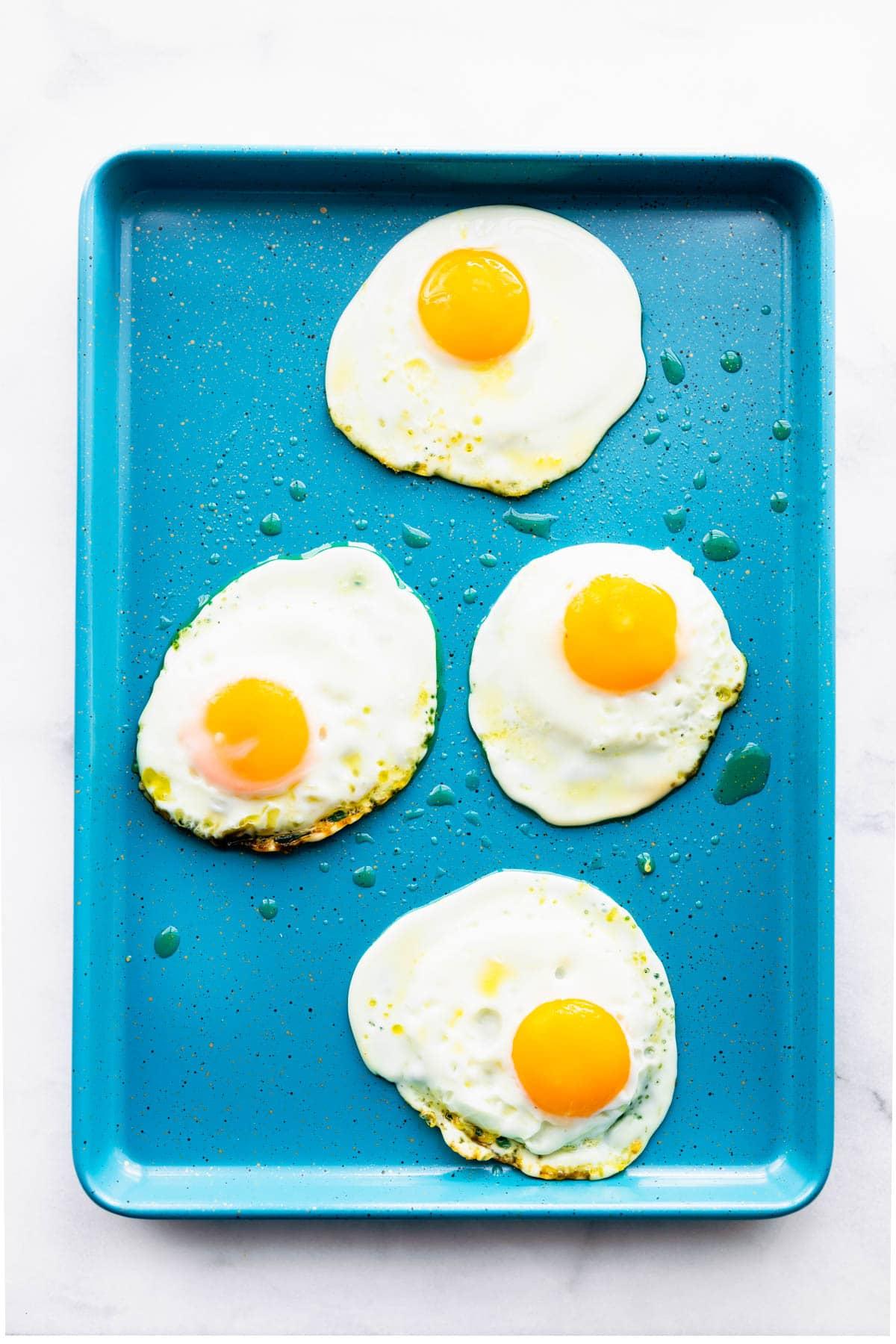 4 olive oil fried eggs on rectangular blue platter