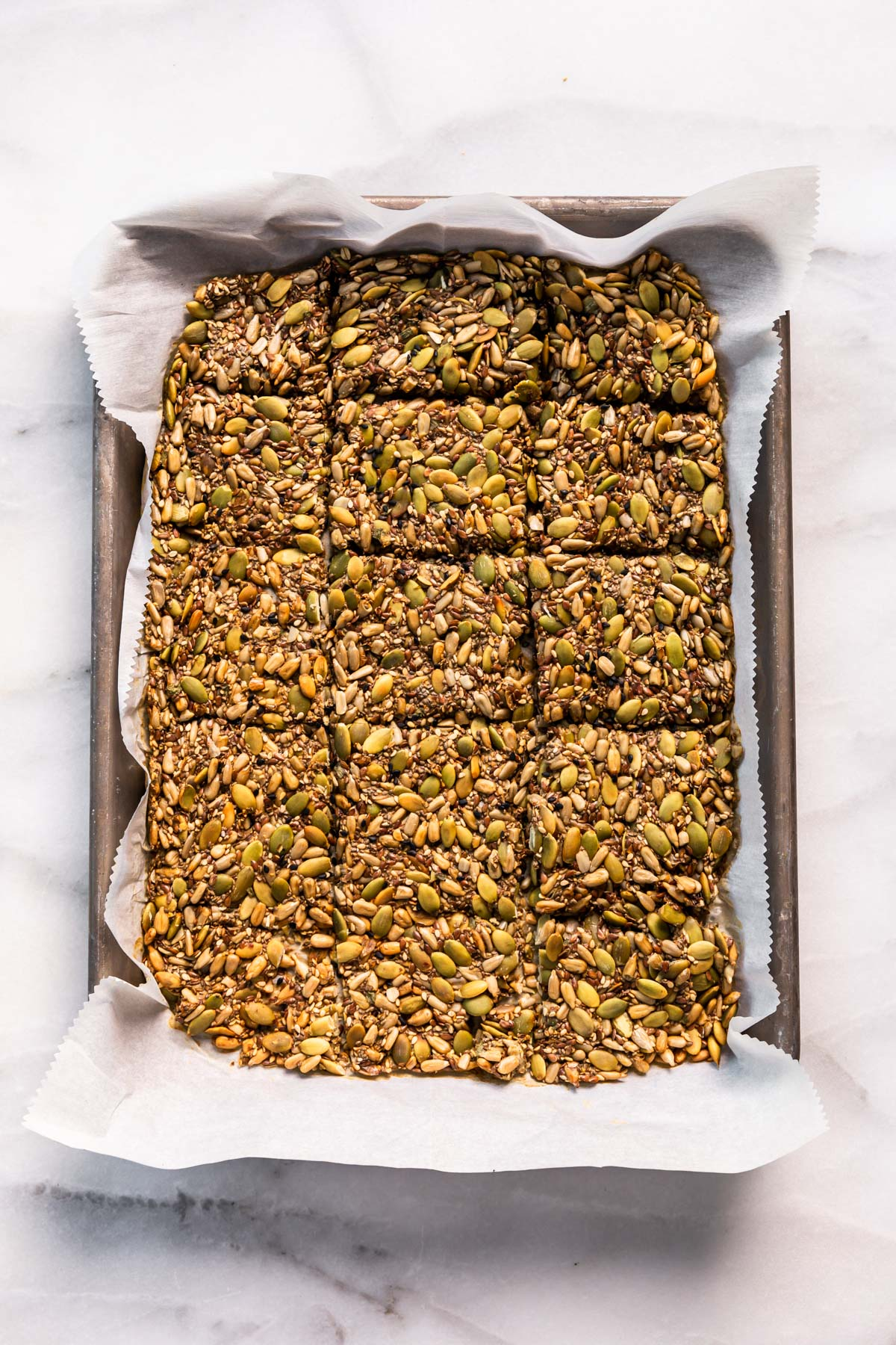 paleo seed healthy crackers on parchment lined baking sheet