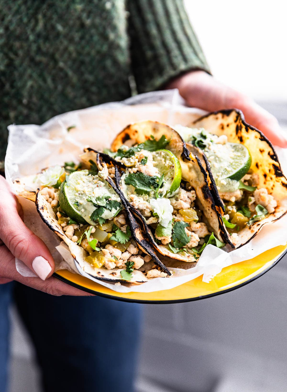 woman holding platter of homemade turkey tacos