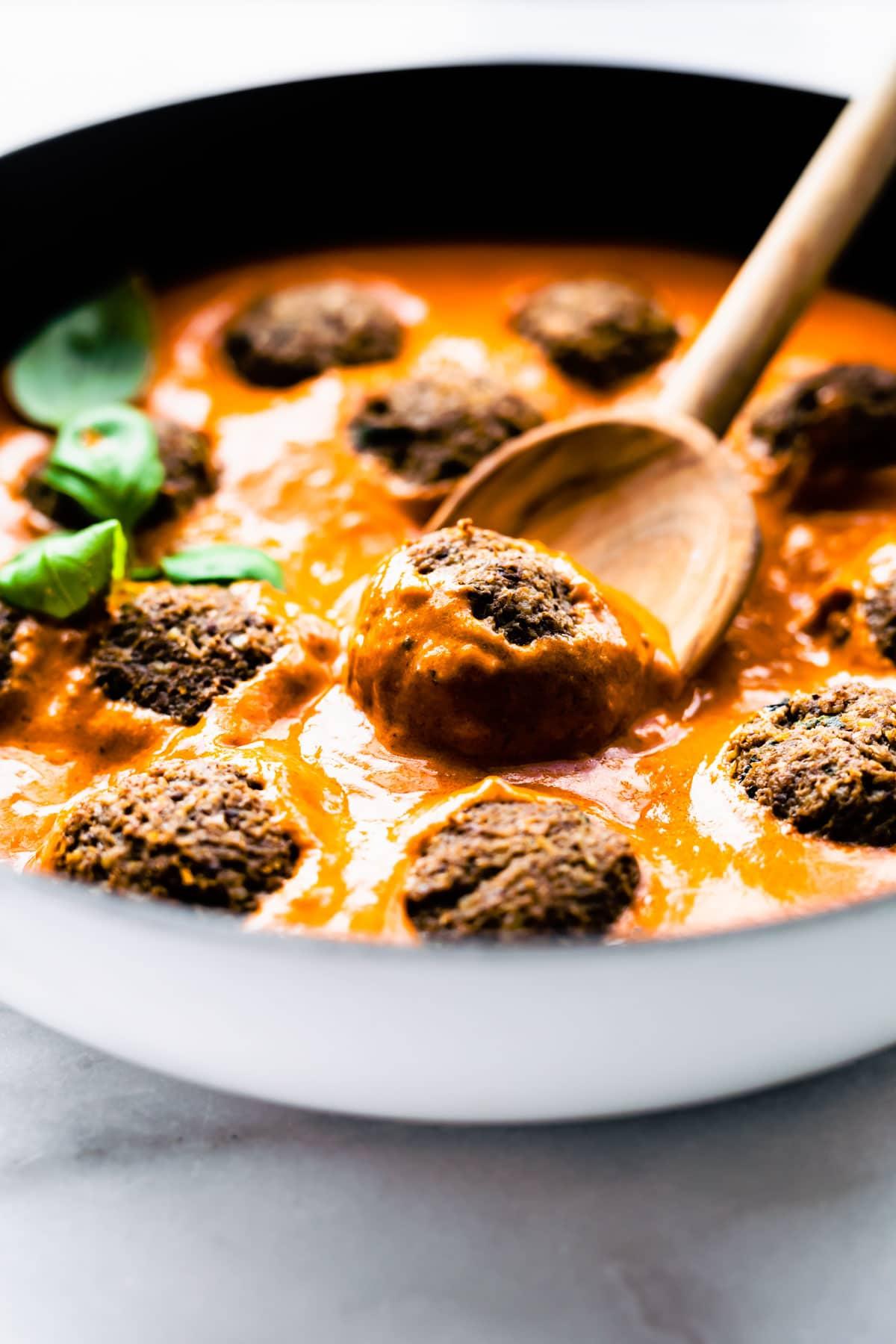 meatballs in pan and sauce with spoon. vegan meatballs