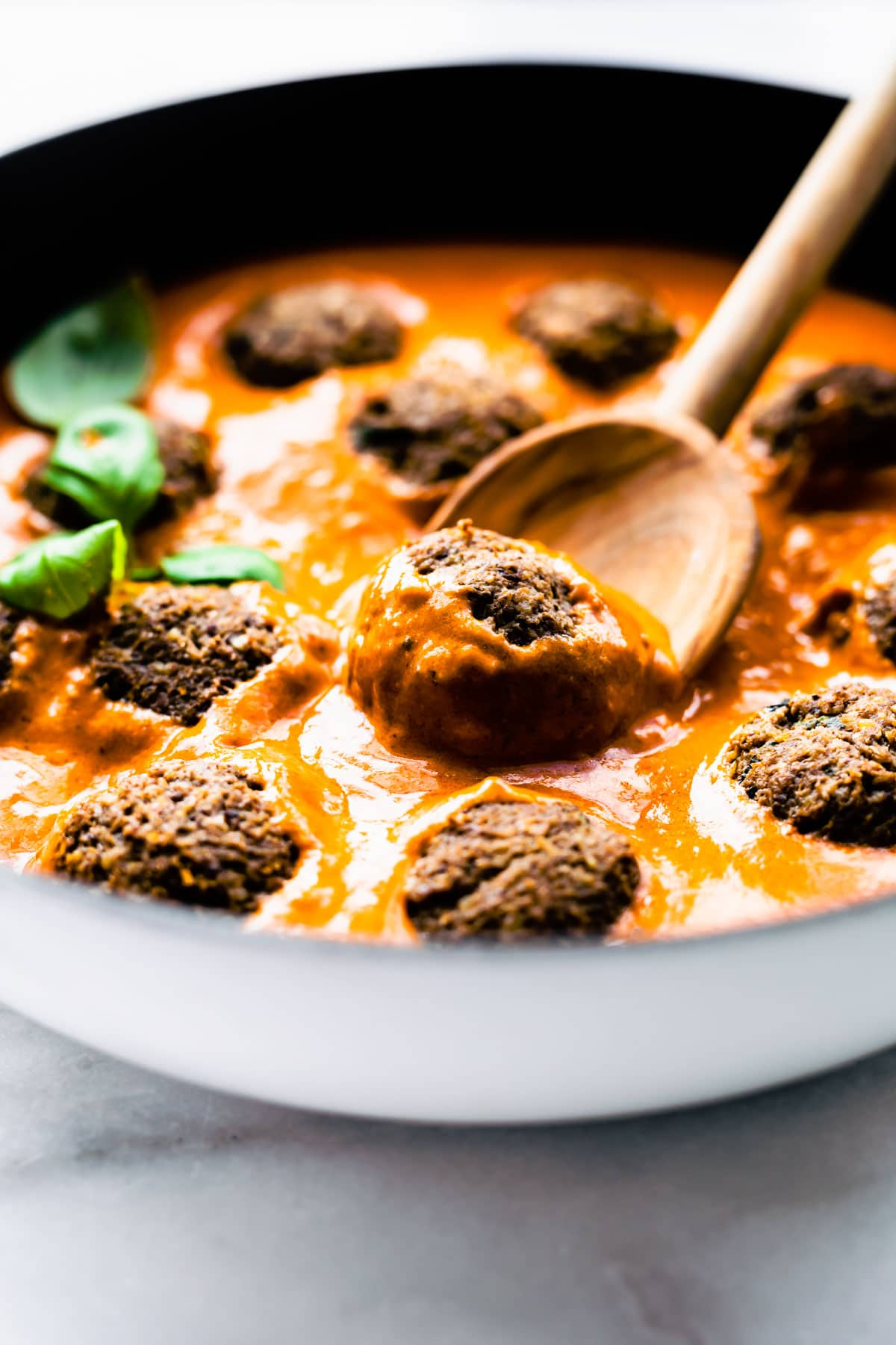 close up: vegan mushroom meatballs in skillet of orange colored pasta sauce