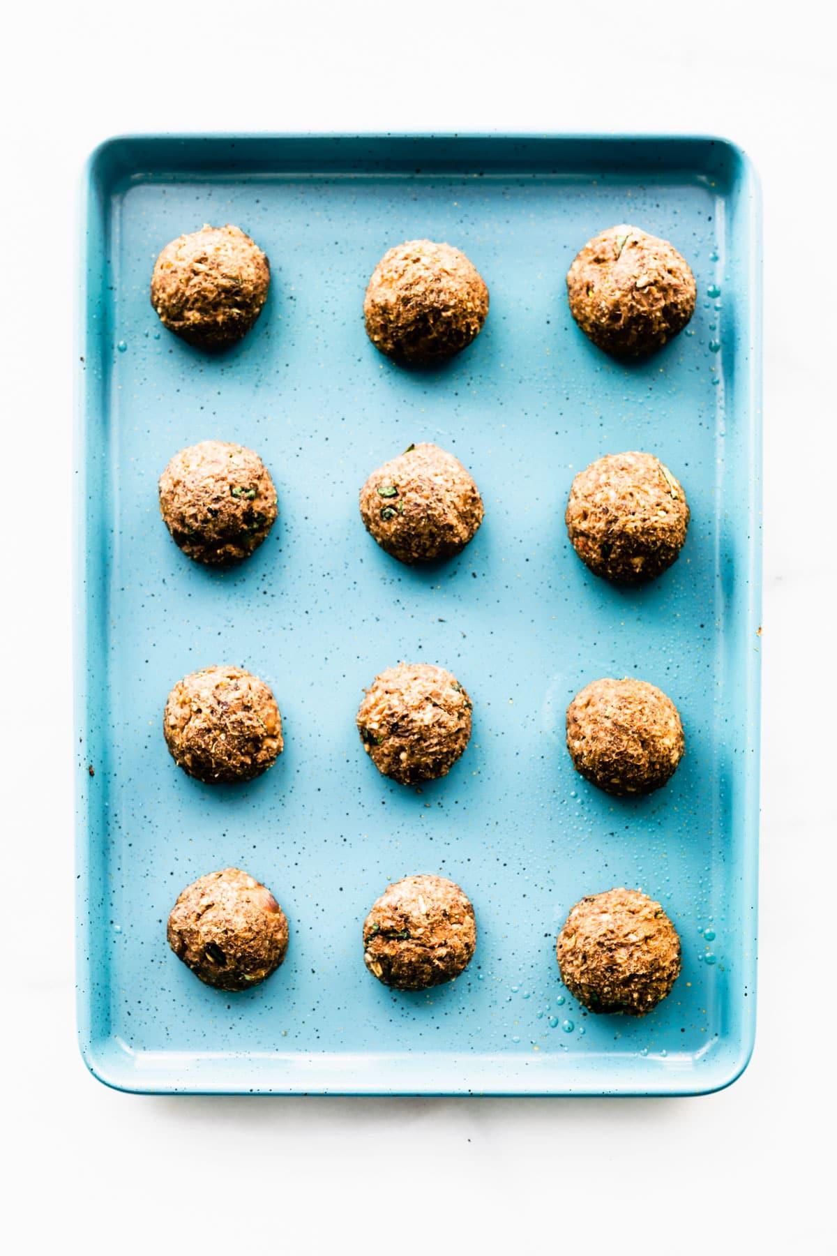 mushroom meatballs on blue baking sheet