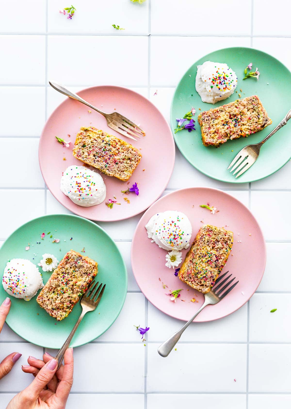 ice cream bread with colored sprinkles on mint green and pink plates with a fork