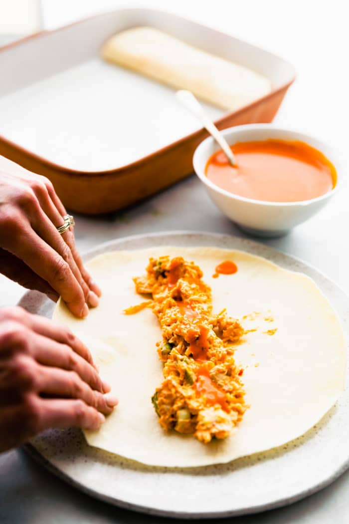 woman's hands rolling tortillas for easy enchilada recipe