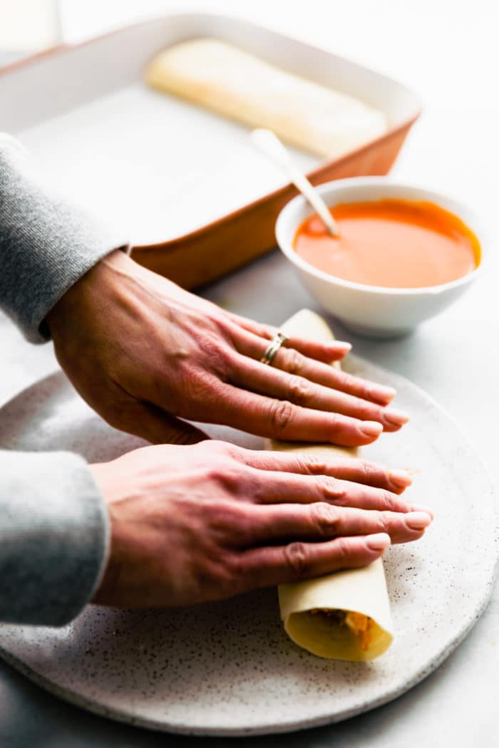 woman's hands rolling gluten free tortillas for enchiladas