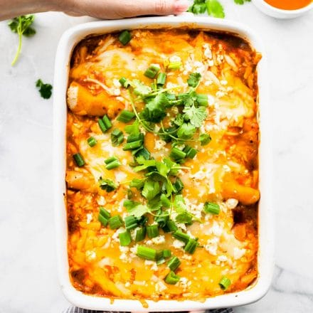 easy enchiladas casserole in rectangular white baking dish