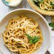overhead photo shows bowl of tender pasta with vegan garlic sauce