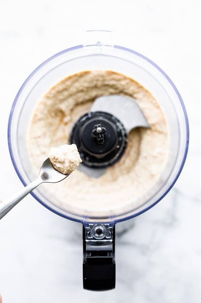 overhead photo: ingredients in food processor to make garlic walnut sauce