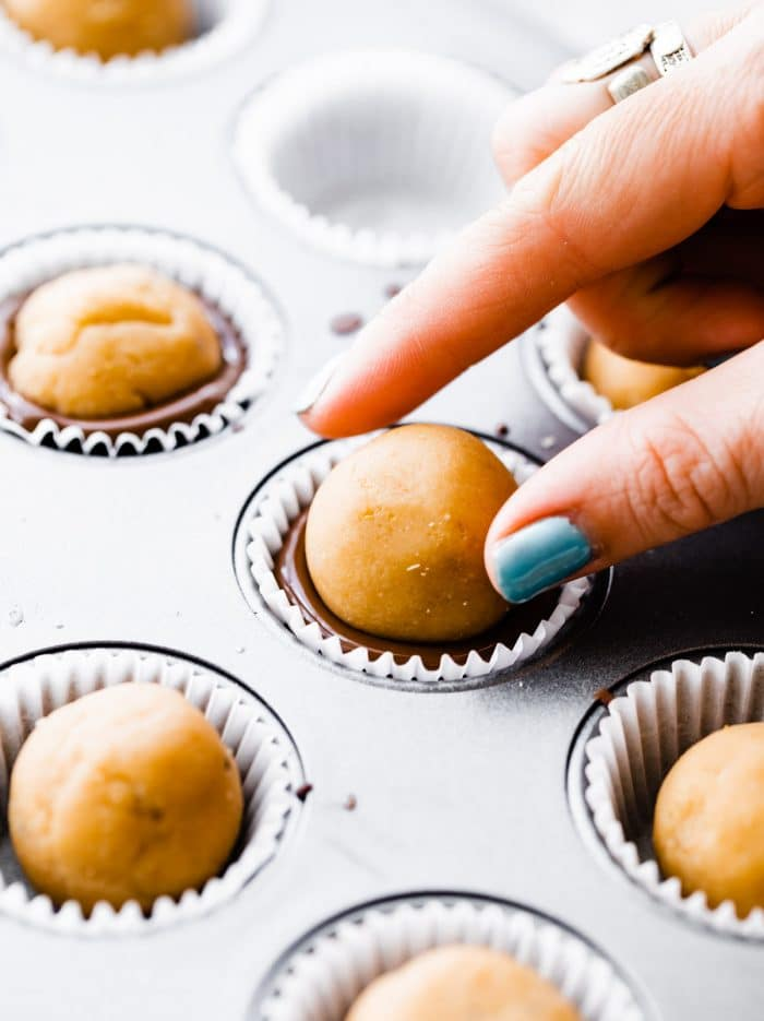 woman pressing edible cookie dough into a chocolate filled muffin liner