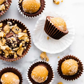 vegan edible cookie dough chocolate cups, some topped with nuts