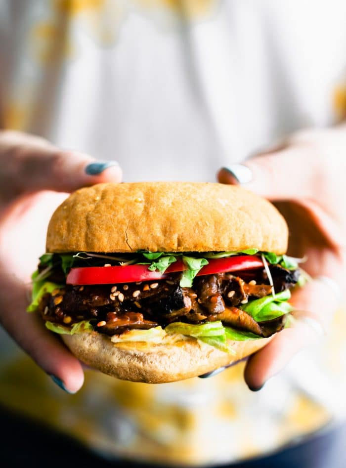 woman's hands holding a veggie steak mushroom burger topped with red bell pepper, sprouts, and lettuce