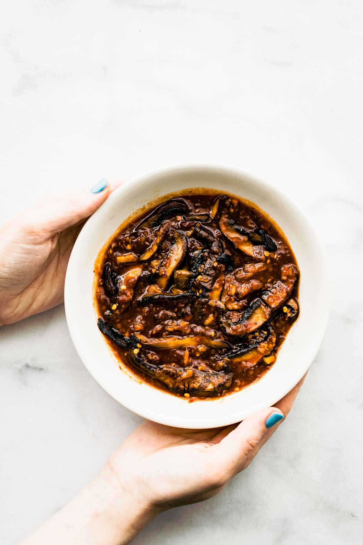 mushroom in a bowl with asian BBQ marinade. Woman is holding the bowl