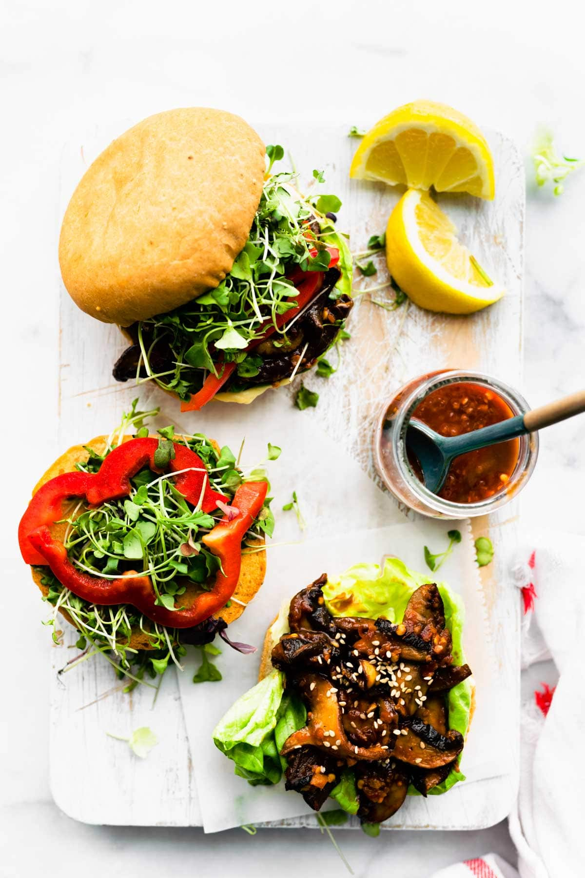 open face mushroom burger with sauce in a container and lemon on side