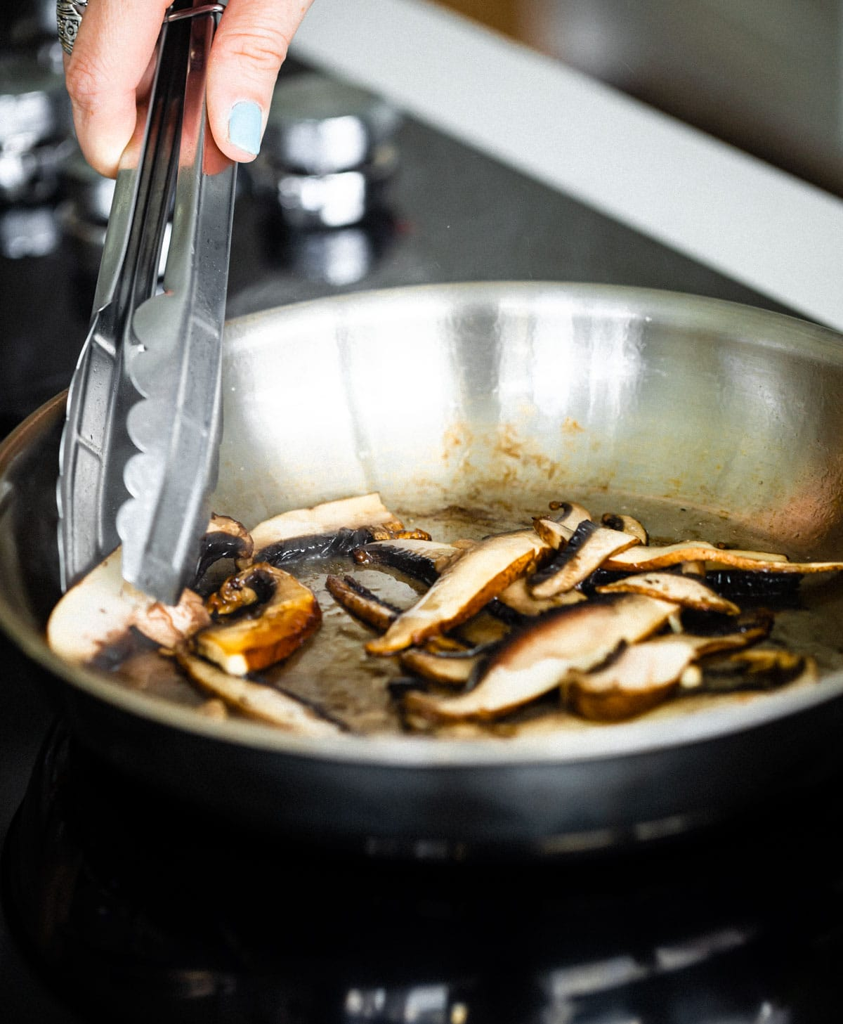 mushrooms in pan with oil. Woman holding tons to flip the sliced mushrooms