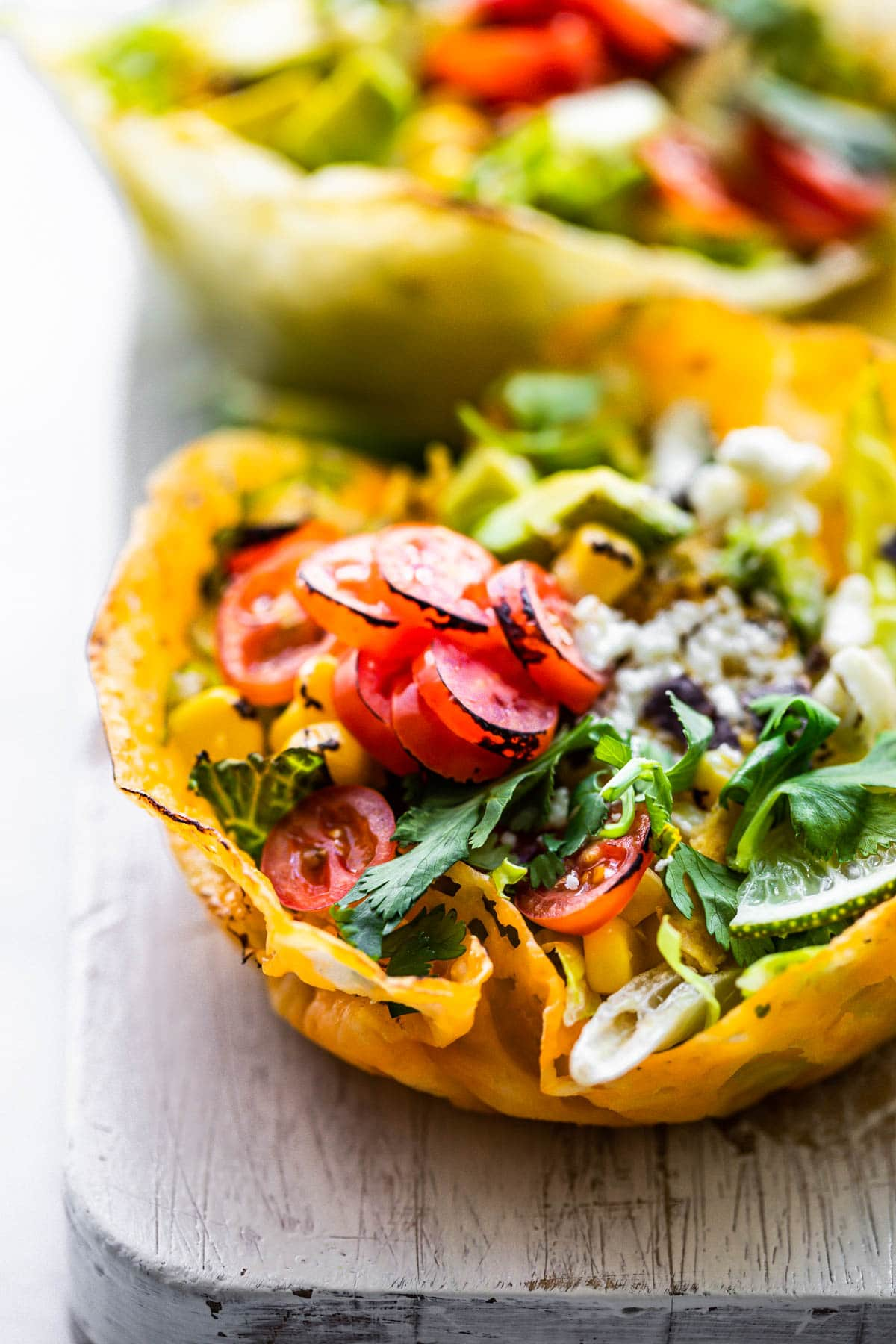 healthy salad with fresh vegetables in a baked cheese bowl