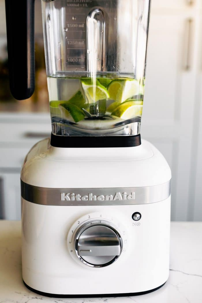 lime wedges and water in a white KitchenAid blender