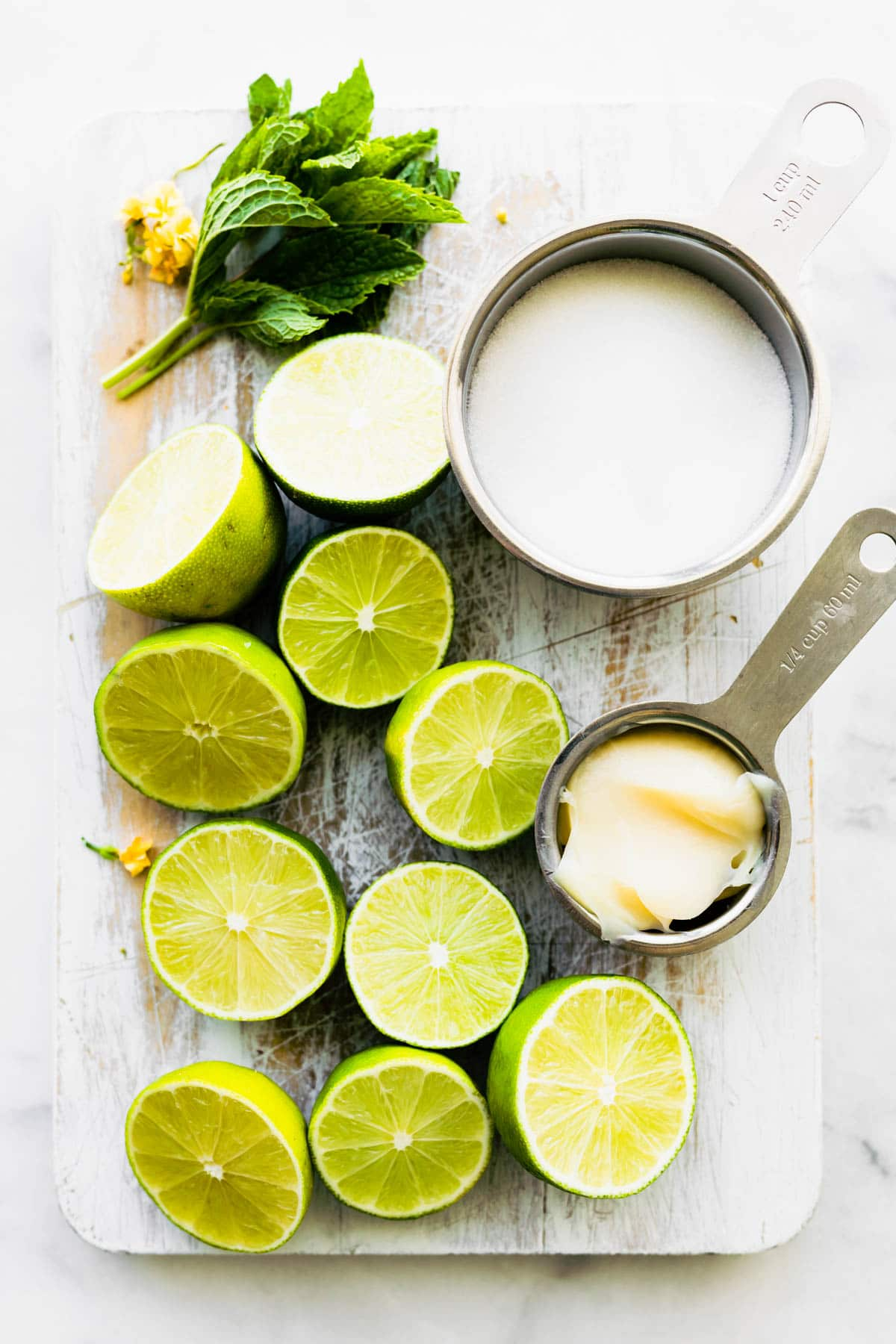 overhead photo: vegan condensed milk, fresh mint and limes cut in half on wooden cutting board