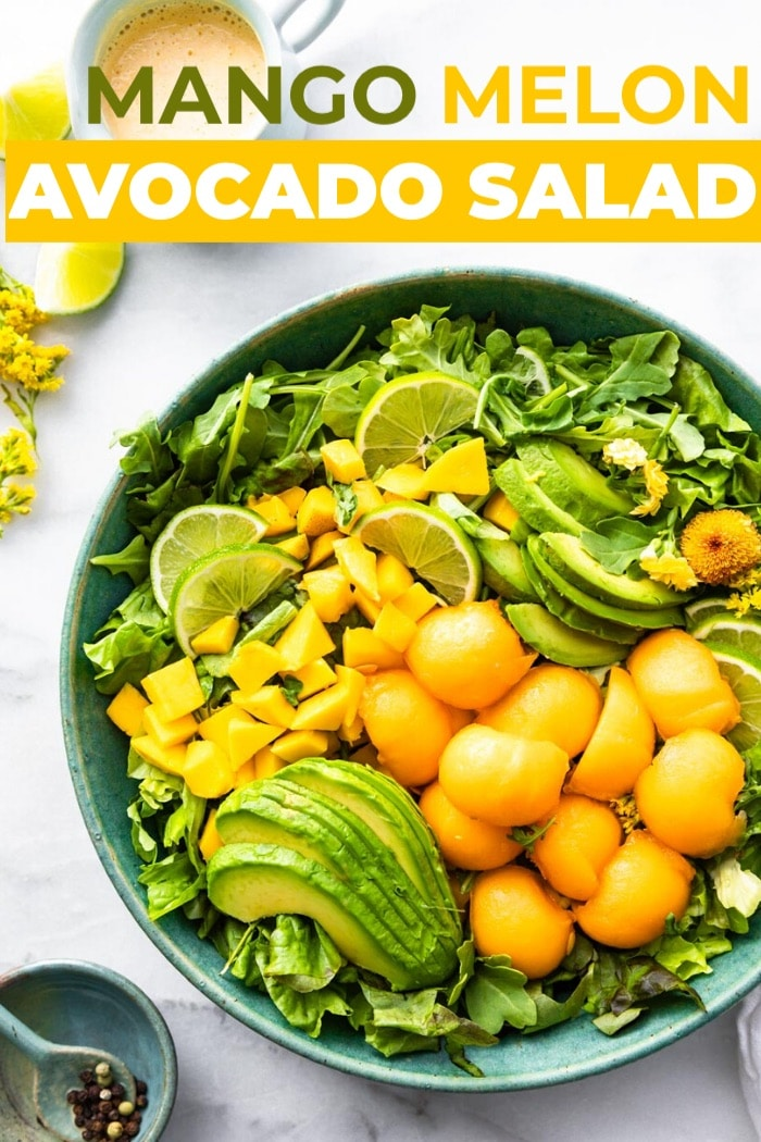 bowl of healthy fruit salad with pieces of mango avocado and cantaloupe with title in white and orange above