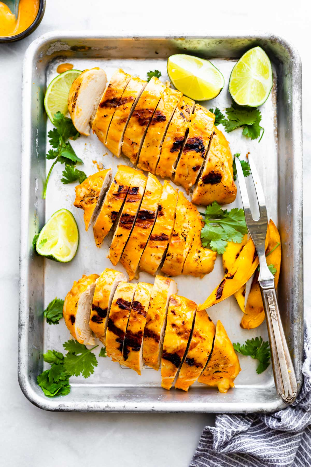 overhead photo: 3 grilled chicken breasts, cut into slices, arranged on metal sheet pan