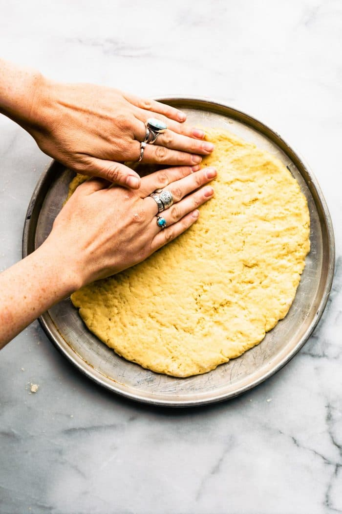 woman's hands pressing yeast free pizza dough into a pizza pan