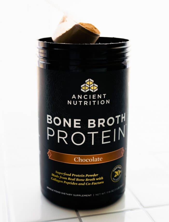 canister of Ancient Nutrition bone broth protein powder (chocolate flavor)