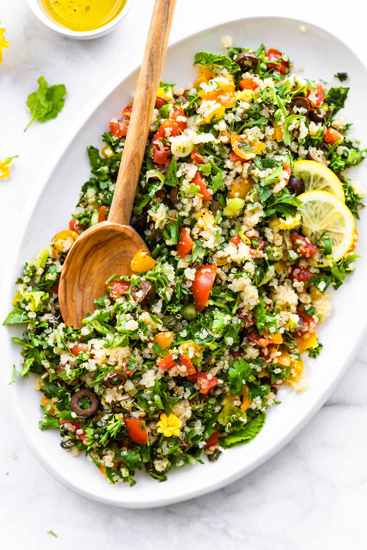 beautiful fresh tabouli salad on white platter with wooden spoon for serving