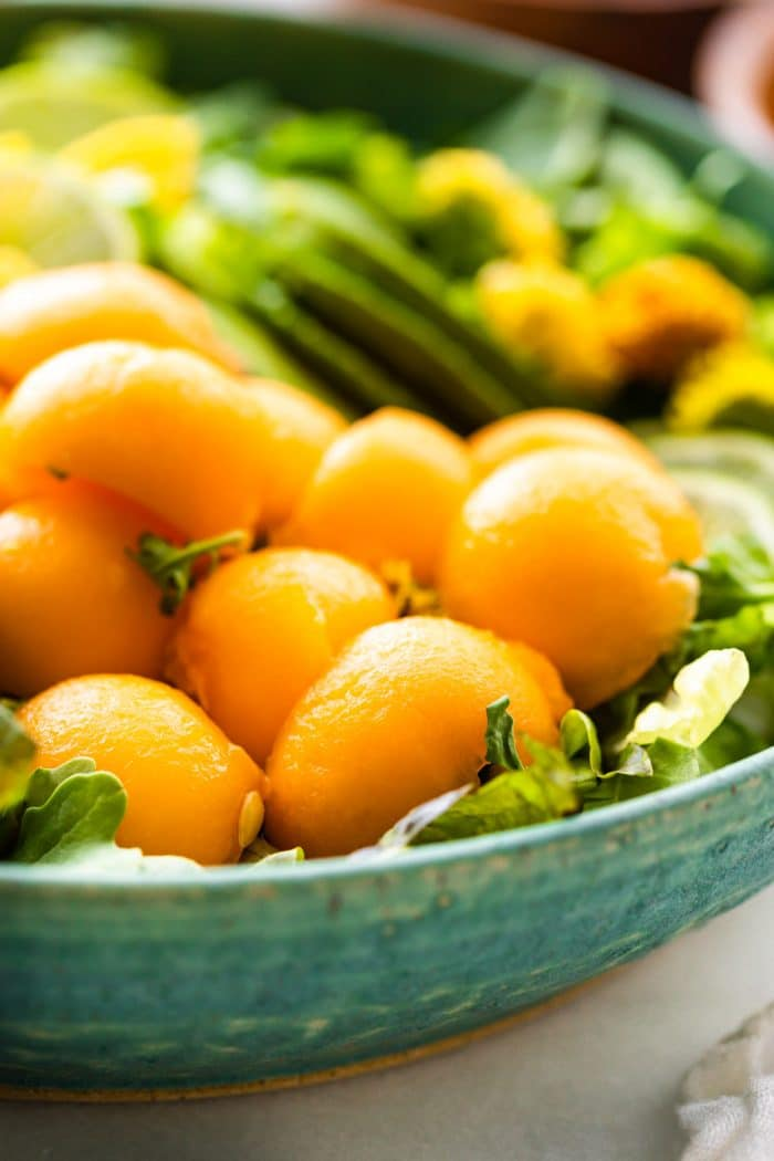 close up: balls of mango and melon with slices of avocado in a salad