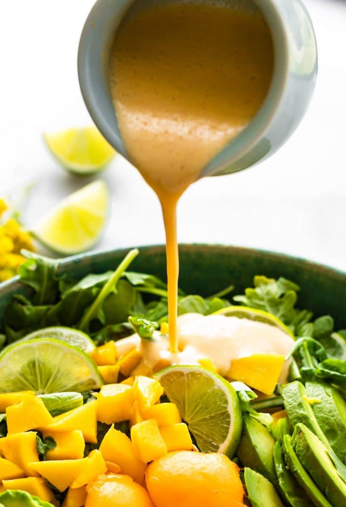 pouring melon dressing over a mango avocado salad
