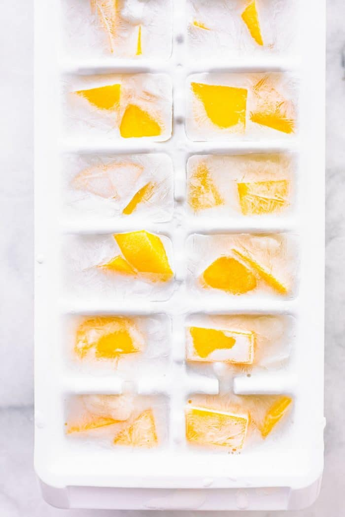 coconut milk ice cubes with pieces of mango frozen in them