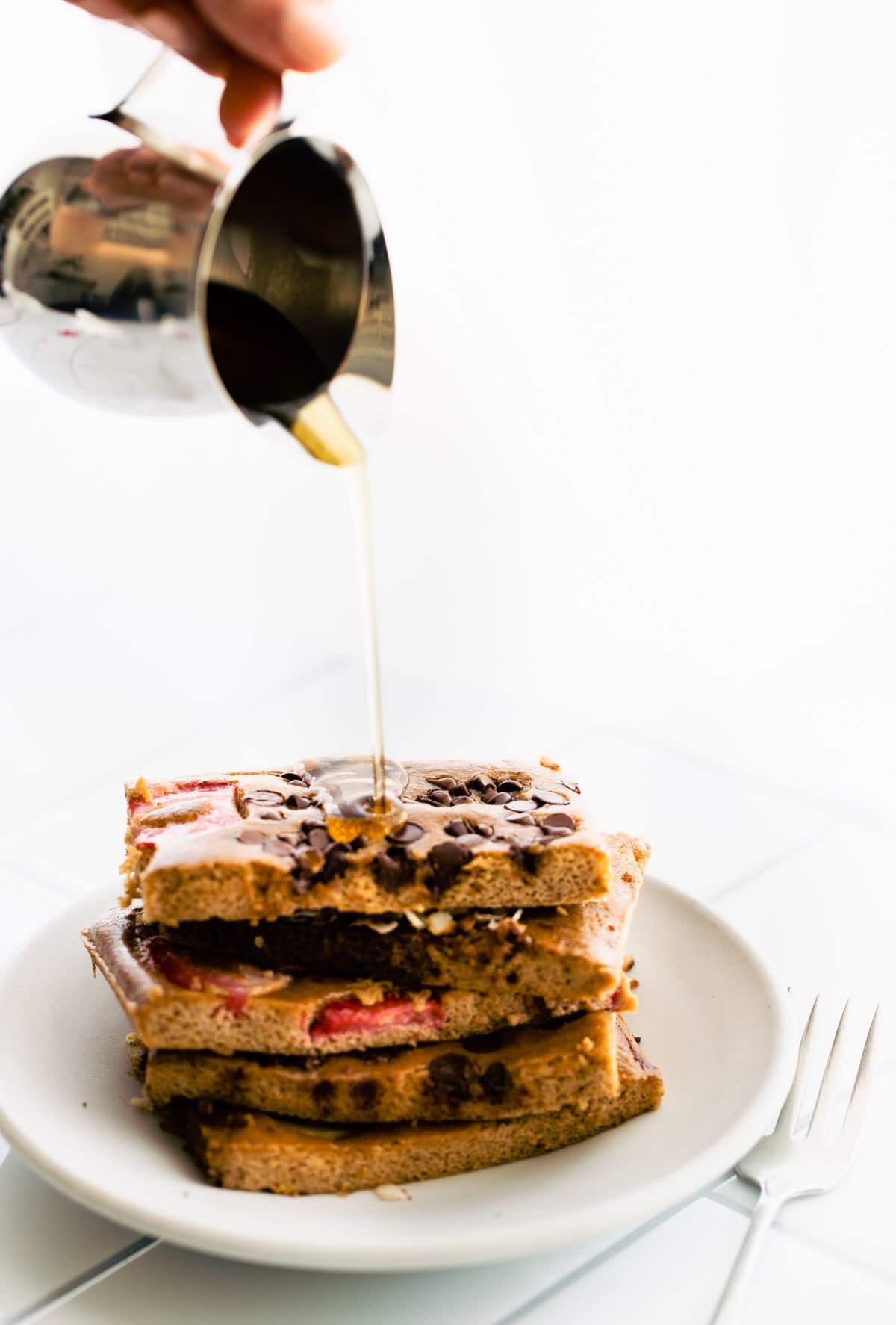 pouring syrup over stack of sheet pan pancakes on a plate