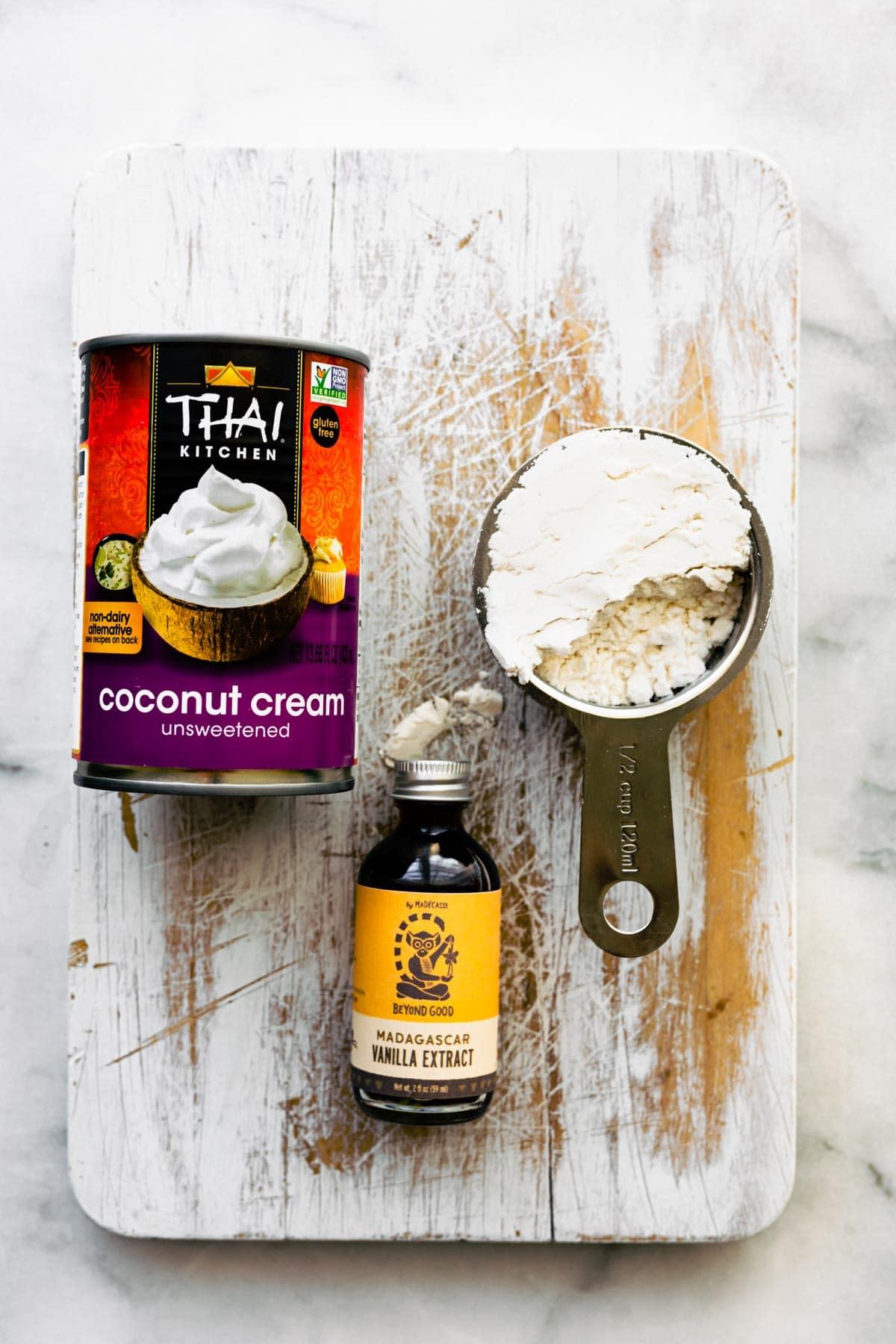 vegan condensed milk ingredients on wooden board: coconut cream, vanilla extract, powdered sugar
