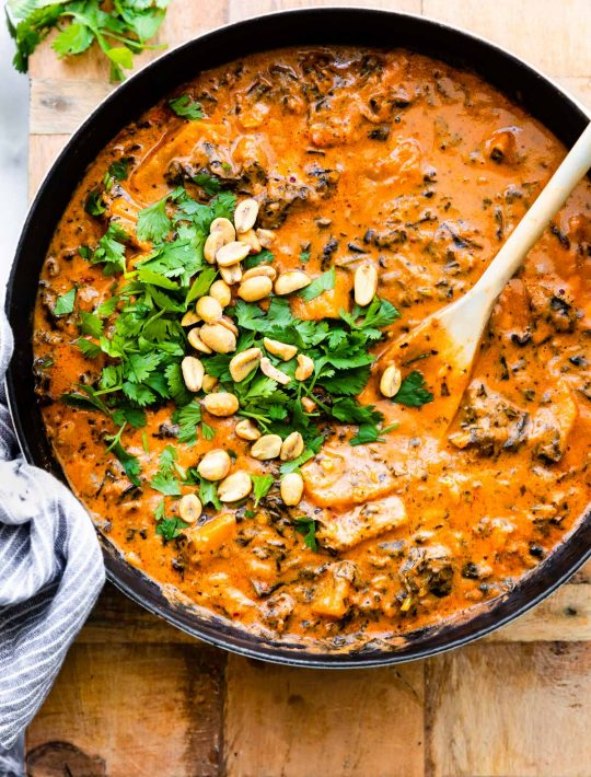overhead photo: large pot of peanut stew; wooden spoon stirring fresh herbs in
