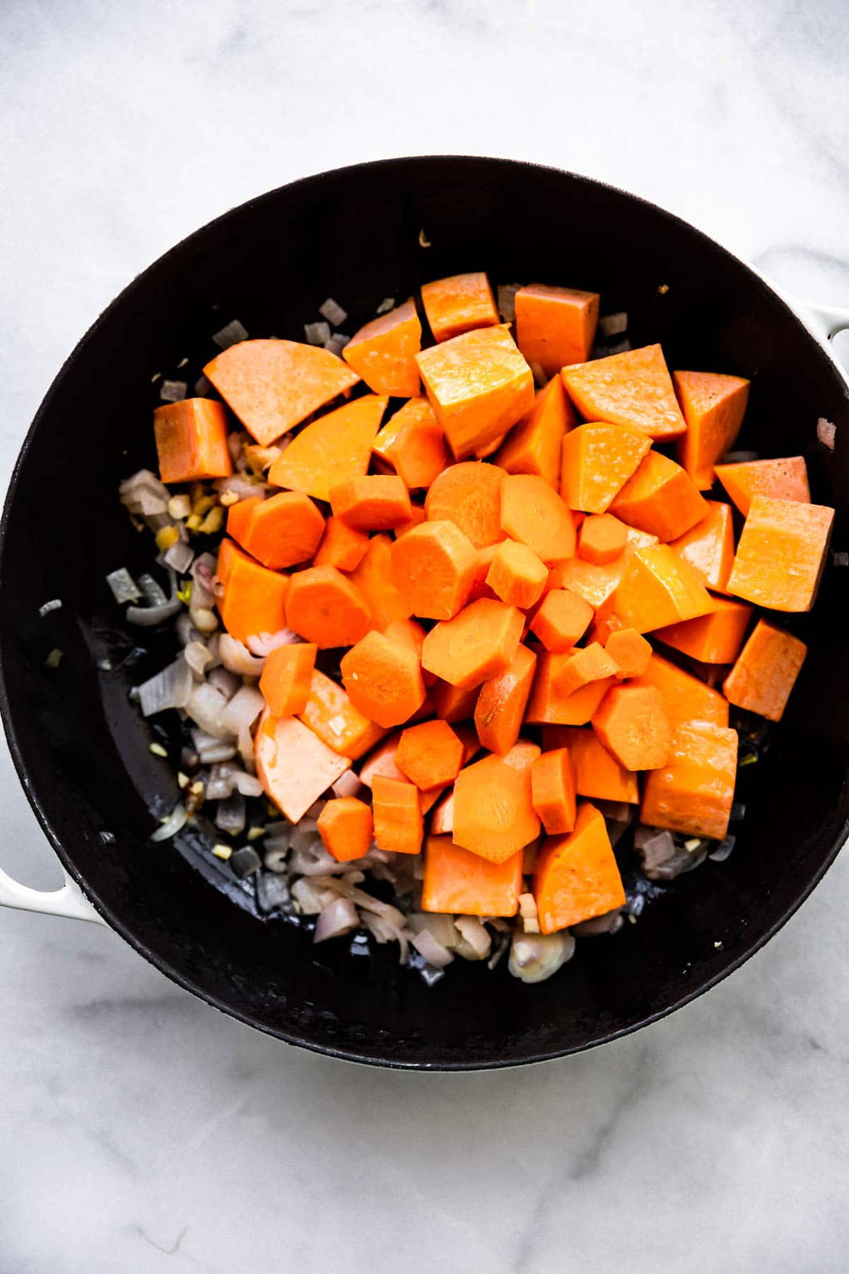 overhead photo: chopped carrots and sweet potatoes in black pot